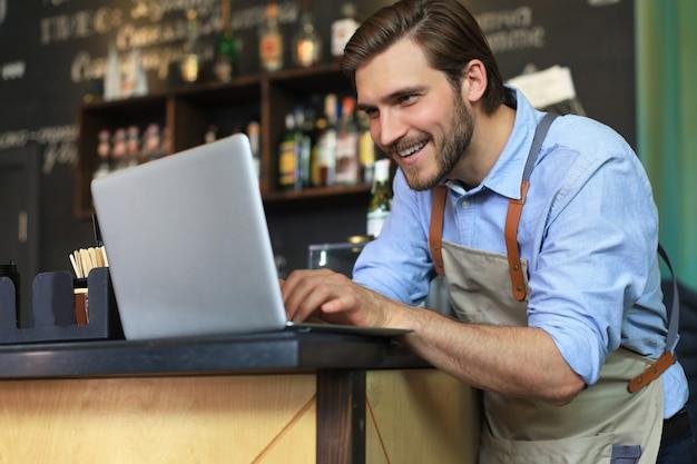 Restaurantmanager, der am laptop arbeitet und den gewinn zählt.