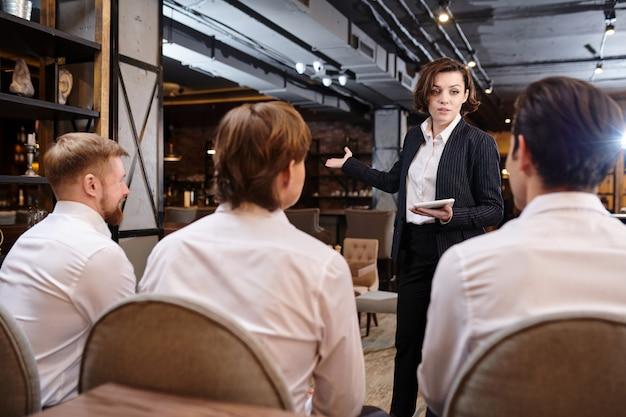 Restaurantmanager erklärt den kellnern die aufgaben