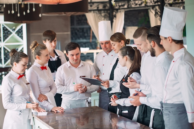 Restaurantmanager und seine mitarbeiter auf der terrasse im austausch mit dem küchenchef im restaurant,