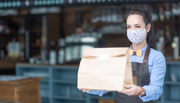 Restaurantmitarbeiter übergibt während der covid-19-pandemie lebensmittel, die in einer papiertüte mit gesichtsmaske verpackt sind.