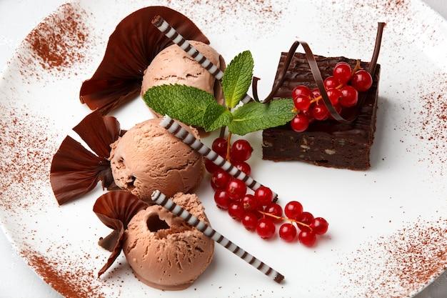 Restaurantnachtisch mit der schokoladeneiscreme, kuchen und roter johannisbeere verziert mit schokoladenchips