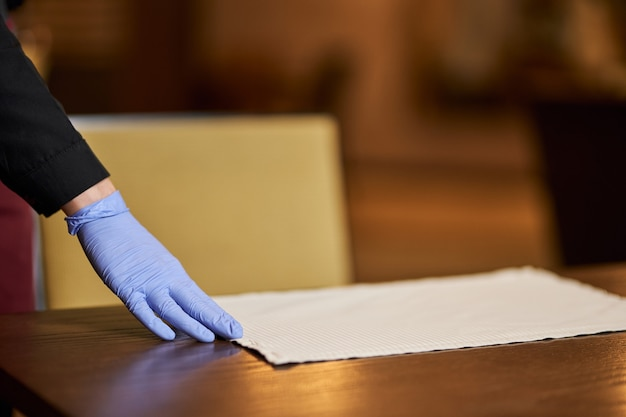 Restaurantpersonal mit handschuhen zum aufstellen von tischen