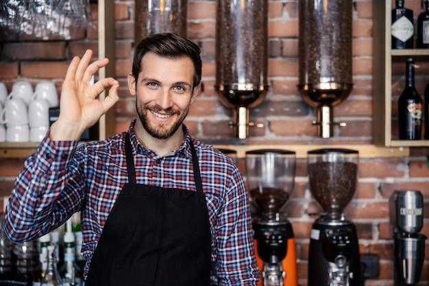 Restaurantservice und café. ein erwachsener männlicher kellner steht hinter einer bar in einem café und zeigt ein handzeichen der zustimmung. ein angenehmes lächeln und eine positive einstellung. cafeteria und kaffeezubereitung