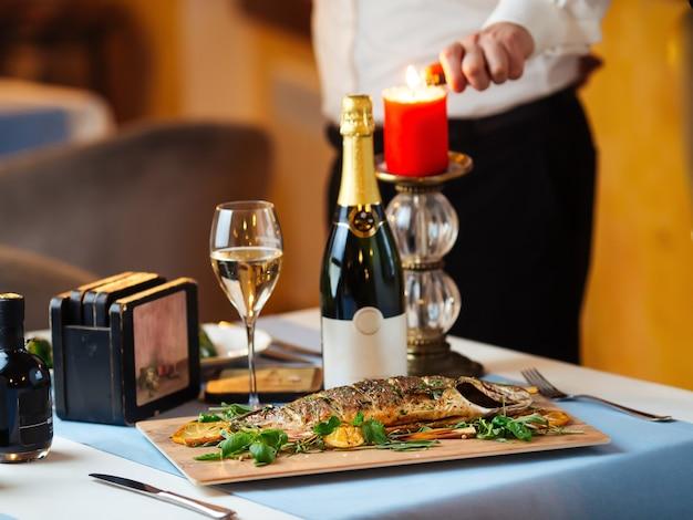 Restauranttisch mit gegrilltem wolfsbarsch mit kellner, der eine kerze auf dem tisch anzündet