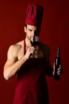 Restaurantweinherstellung männlicher sommelier, der rotwein verkostet, sexy koch in burgunder-kochmütze und schürze mit