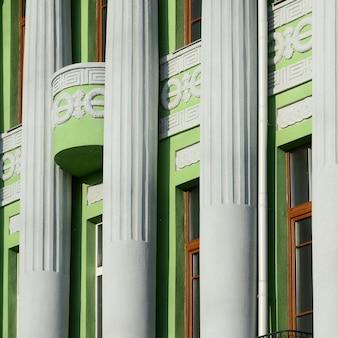 Restauriertes altes mehrstöckiges gebäude mit antiken säulen, grün gestrichen