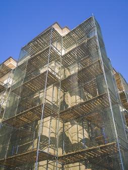 Restaurierung des alten gebäudes. das gebäude ist zum schutz mit einem reparaturgitter abgedeckt