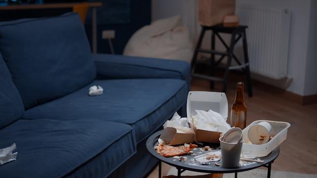 Reste von leeren bierflaschen und servietten der pizza auf dem elendstisch und dem ungesunden lebensstil des bodens unordentlich ...