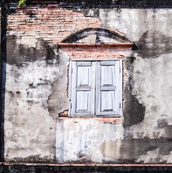 Retro- altes gealtertes fenster der weinlese und braune farbe maserten lehmziegelsteinblockwand