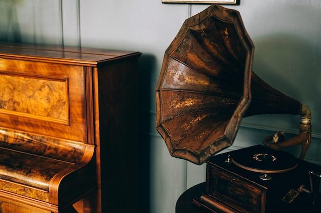 Retro altes grammophonradio mit hornlautsprecher steht mit altem klavier