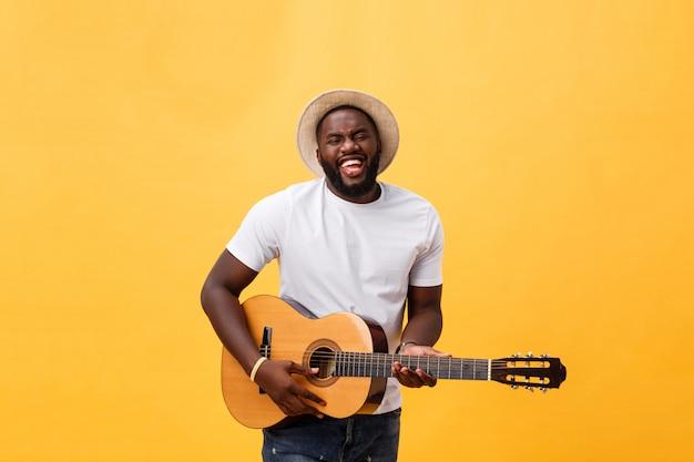 Retro- angeredeter gitarrist des afroamerikaners, der die akustikgitarre lokalisiert auf gelbem hintergrund spielt.