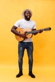 Retro- angeredeter gitarrist des hübschen afroamerikaners, der die akustikgitarre lokalisiert auf gelbem hintergrund spielt.