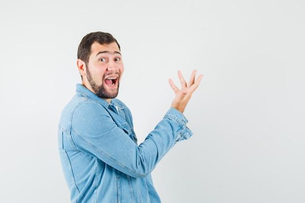 Retro-art-mann, der hand auf seltsame weise in jacke, t-shirt erhebt und verrückt aussieht. .