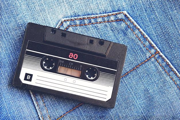 Retro- audiokassette der weinlese auf blue jeans, nahaufnahme. medientechnologien der letzten 80er jahre. konzeptbild zur veranschaulichung der erinnerungen an die vergangenheit. der blick von oben.