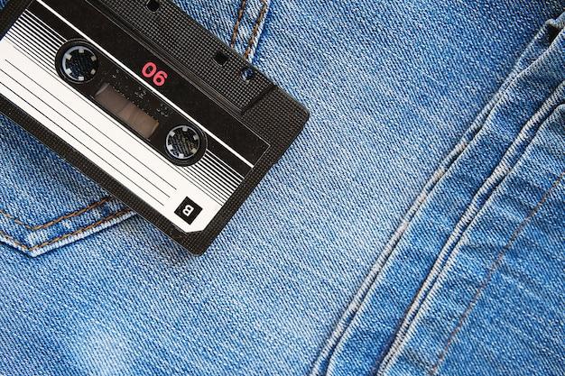Retro- audiokassette der weinlese blue jeans, nahaufnahme. medientechnologien der letzten 80er jahre. konzeptbild zur veranschaulichung der erinnerungen an die vergangenheit. der blick von oben.