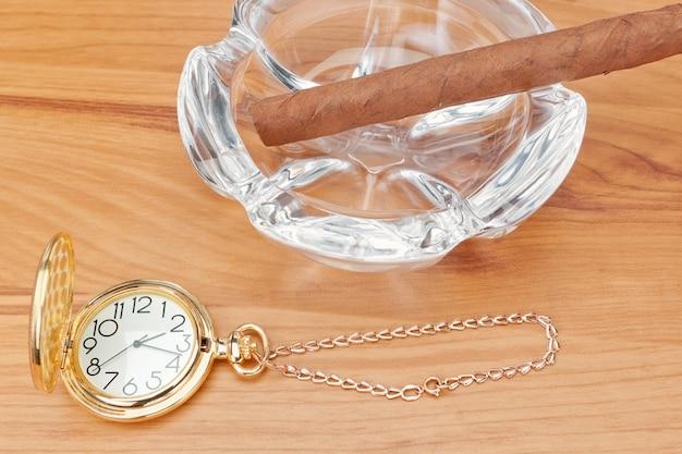 Retro-bild der goldenen taschenuhr und einer havanna-zigarre im aschenbecher. in den warmen gelbtönen.