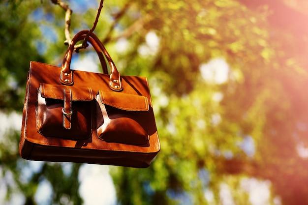 Retro braune mann-ledertasche im hellen bunten sommerpark, der an blättern hängt