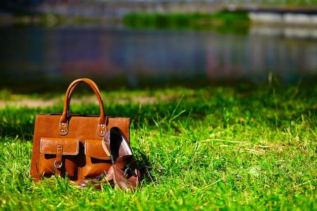 Retro braune schuhe und mann ledertasche im hellen bunten sommergras im park