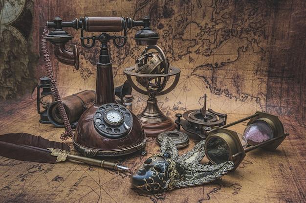 Retro bronze telefon und alte sammlung auf der alten weltkarte
