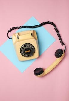 Retro-drehtelefon aus den 80ern auf einer farbigen pastelloberfläche. draufsicht, minimalismus