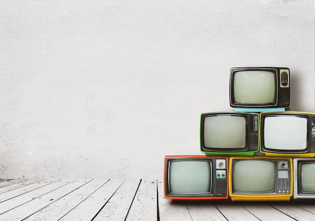 Retro-fernseher stapeln sich auf boden in altem raum mit weißer wand