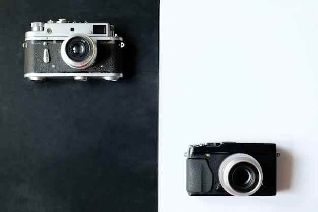 Retro film 35 mm fotokamera und moderne digitalkamera, die auf weißer und schwarzer oberfläche liegen