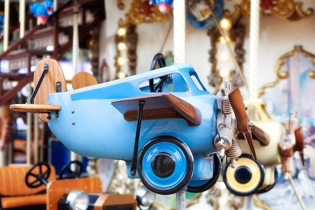 Retro- flugzeug der alten spielzeugweinlese des flugzeuges. kinder vintage blau flugzeug. kinderkarussell. kinderspielzeug. kleiner pilot. altes flugzeug, doppeldecker. aviation day. flugzeuge und modellflug hobby-konzept.