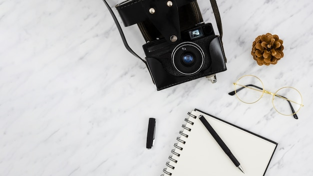Retro- fotokamera der draufsicht mit einem notizbuch