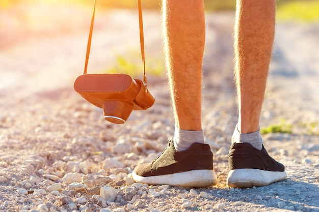 Retro- fotokamera der füße mann und der weinlese im freien reise-lebensstilurlaubkonzept und -tourismus