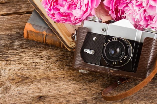 Retro-fotokamera mit büchern und pfingstrosenblumen auf holztisch