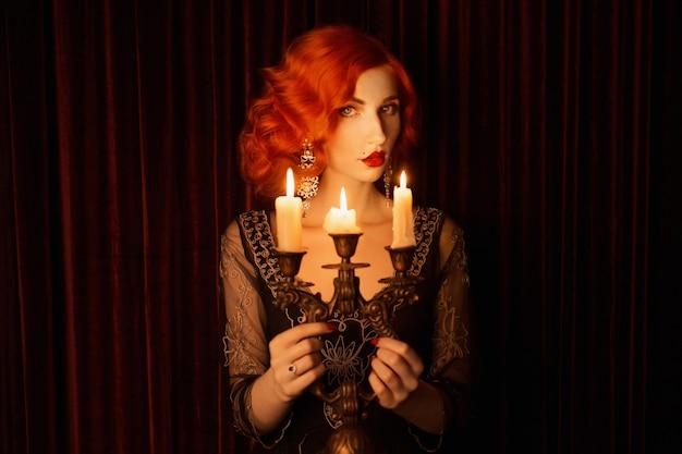 Retro-frau mit roten verworrenen haaren im schwarzen vintage-kleid. weinlese rothaarige frau mit roten lippen halten kerzenhalter mit brennenden kerzen. noir mode. kerzen brennen im kerzenhalter. noir porträt. 1920er jahre