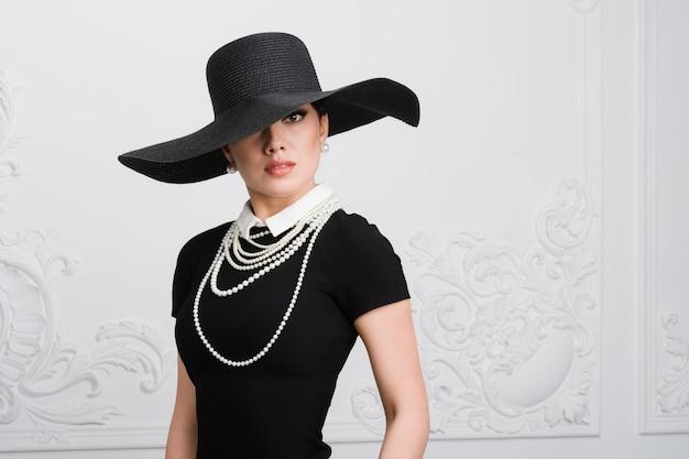 Retro frauenporträt. vintage style girl mit altmodischem hut, frisur und make-up