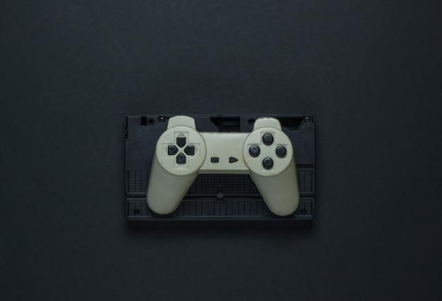 Retro gamepad und videokassette auf einem schwarzen hintergrund. draufsicht