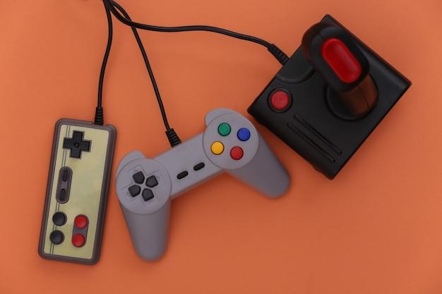 Retro-gamepads und joysticks auf orangem hintergrund. videospiel, spiele der 80er jahre. flache lage, ansicht von oben. platz kopieren