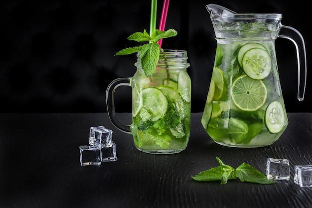 Retro- glasgefäß und krug limonade mit gurke und minze auf holztisch. eiswürfel