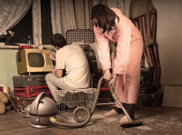 Retro-hausfrau in ihrem morgenmantel und hausschuhen, die ein unordentliches wohnzimmer mit einem vintage-staubsauger säubert, während ihr mann auf einem alten fernsehgerät fernsieht