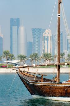 Retro historisches boot mit unscharfem panoramablick auf moderne skyline von doha und grüne palmen auf oberfläche