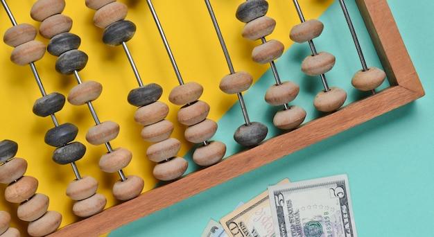 Retro hölzerner abakus, dollarnoten auf einem farbigen papier