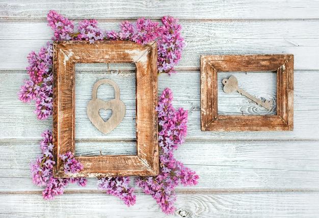 Retro holzrahmen mit herzschloss und schlüsselfederzweigen der lila blumen