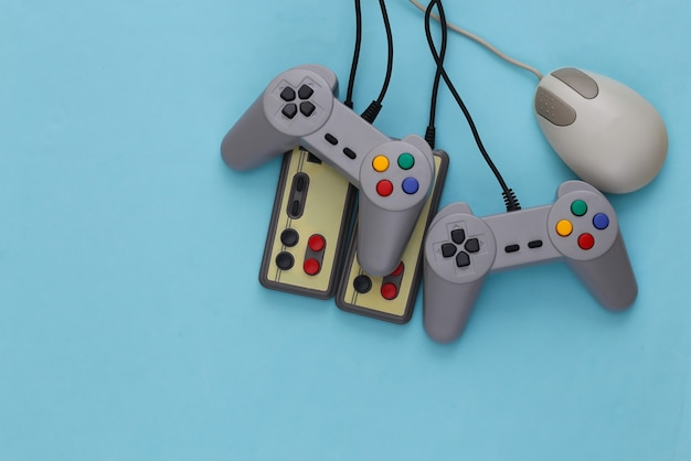 Retro-joysticks und pc-maus auf blau. retro-gaming, spielgeräte, gadgets
