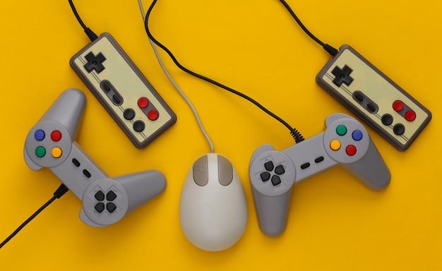 Retro-joysticks und pc-maus auf einem gelb. retro-gaming, spielgeräte, gadgets