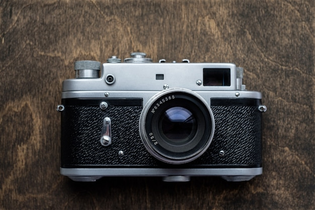 Retro-kamera auf holztischhintergrund, vintage-entfernungsmesser-filmkamera, flache draufsicht