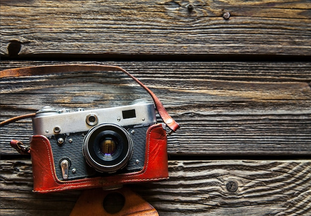Retro-kamera auf holztischhintergrund, weinlesefarbton