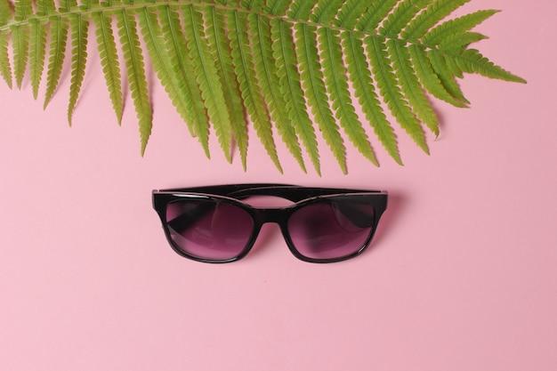 Retro-kamera, farnblatt, muscheln, sonnenbrille auf rosa pastellhintergrund. das konzept von reisen, tourismus, strandresort. draufsicht