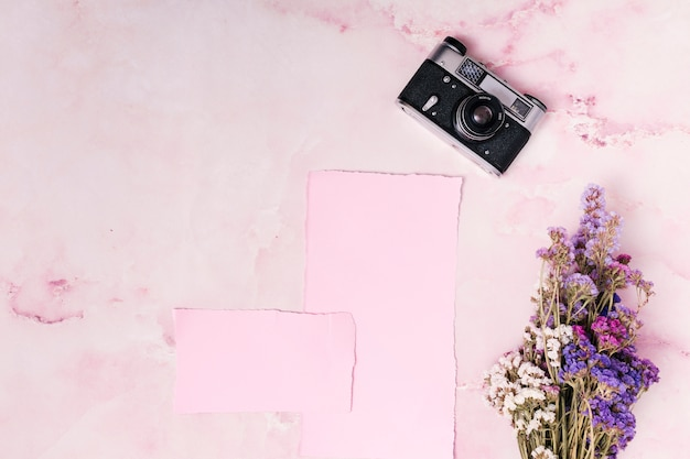 Retro kamera in der nähe von papieren und blumenstrauß