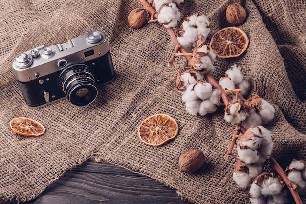 Retro-kamera und baumwolle auf einem ast im rustikalen stil.