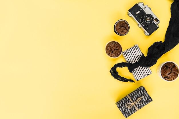 Retro- kamera und kleine kuchen nahe geschenken