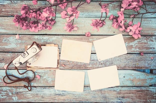 Retro-kamera und leere alte instant-papier fotoalbum auf holztisch mit blumen grenze design - konzept der erinnerung und nostalgie im frühjahr. vintage-stil
