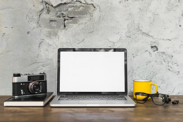 Retro- kamera und offener laptop mit bürobriefpapieren auf holztisch