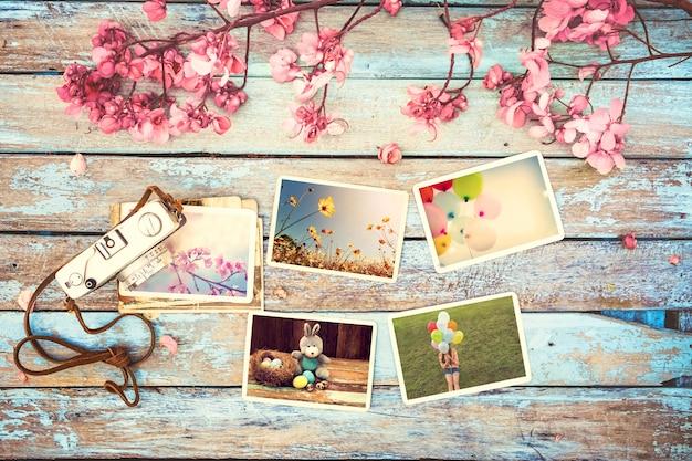 Retro- kamera- und papierfotoalbum auf hölzerner tabelle mit blumengrenzdesign